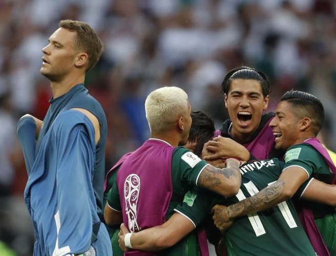 Germany goalkeeper Manuel Neuer walks past as Mexico players celebrate. Image:  Eduardo Verdugo/AP/Press Association Images